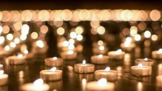 Large group of burning candles placed on the ground by believers